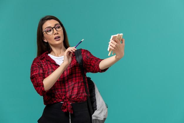 Vista frontale della studentessa che indossa uno zaino in possesso di cavalletto e nappa sulla parete blu chiaro