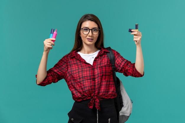 Vista frontale della studentessa che indossa uno zaino in possesso di pennarelli sulla parete blu