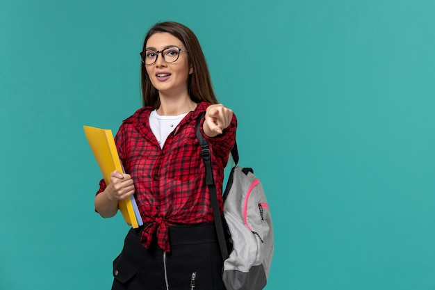 Front view of female student wearing backpack and holding files on blue wall