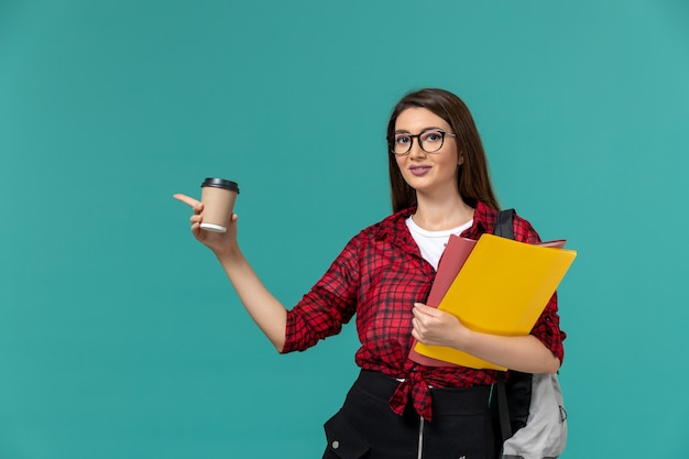 Front view of female student wearing backpack holding files and coffee on blue wall