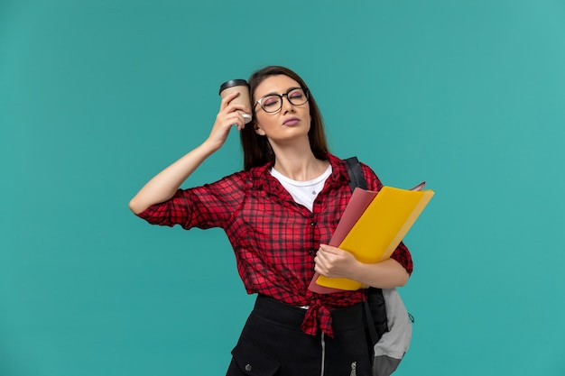 Front view of female student wearing backpack holding files and coffee on the blue wall