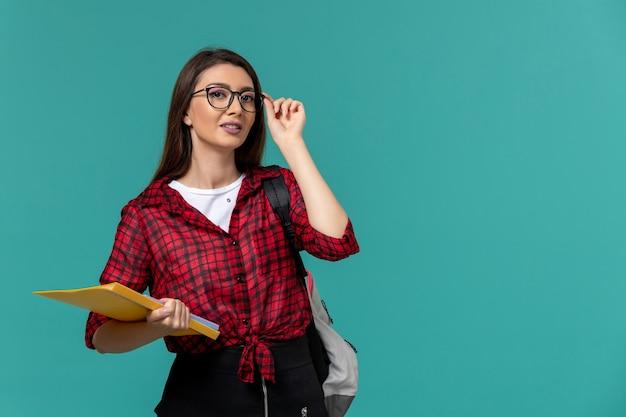 Vista frontale della studentessa che indossa uno zaino e che tiene i file sulla parete azzurra