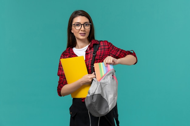 Front view of female student wearing backpack and holding files taking out copybook on the light-blue wall