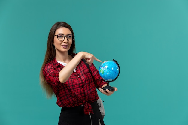 Front view of female student wearing backpack holding little globe on light-blue wall