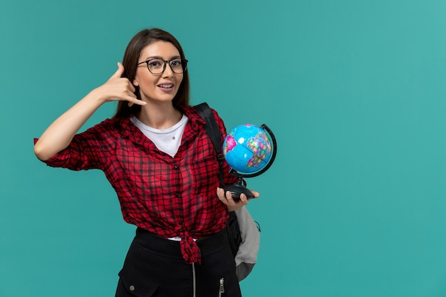 Front view of female student wearing backpack holding little globe on light blue wall