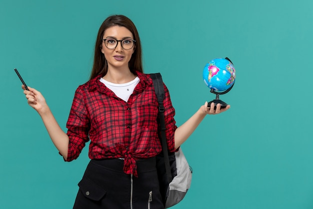 Front view of female student wearing backpack holding little globe and pen on light-blue wall