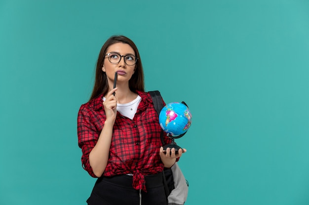 Vista frontale della studentessa che indossa uno zaino che tiene piccolo globo e penna sul muro azzurro