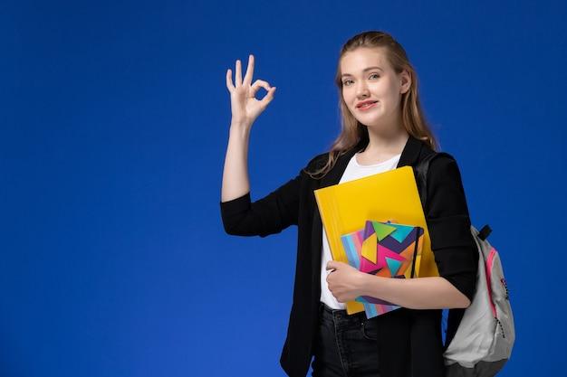 Studentessa di vista frontale in camicia bianca e giacca nera che indossa lo zaino che tiene i file con i quaderni sulla lezione dell'università dell'università della parete blu