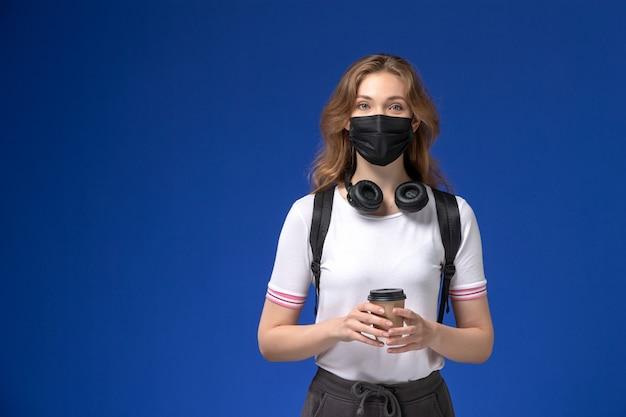Vista frontale della studentessa in camicia bianca che indossa la maschera nera dello zaino e che tiene il caffè sulla parete blu