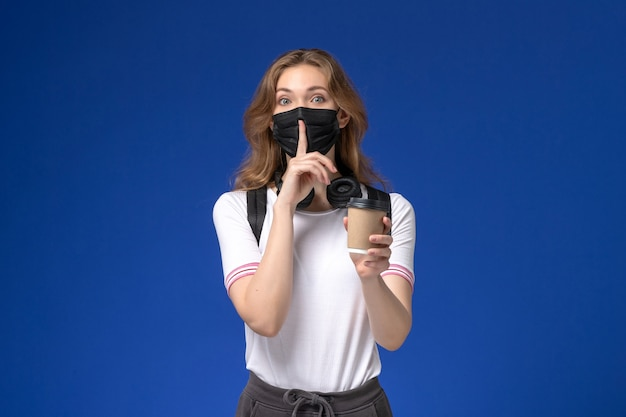 Front view of female student in white shirt wearing backpack black mask and holding coffee on the blue wall