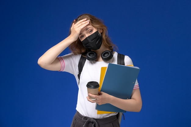 Front view of female student in white shirt wearing backpack black sterile mask holding coffee and files on the blue wall