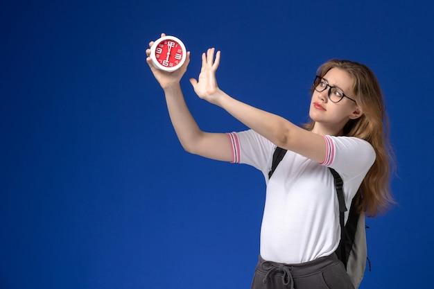 Vista frontale della studentessa in camicia bianca che indossa uno zaino che tiene gli orologi sulla parete blu
