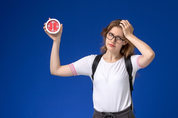 Front view of female student in white shirt wearing backpack and holding clocks on the blue wall