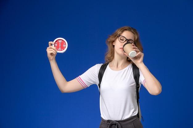 Vista frontale della studentessa in camicia bianca che indossa uno zaino e tiene orologi e caffè sulla parete blu