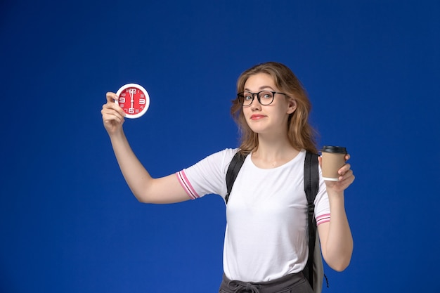 Front view of female student in white shirt wearing backpack and holding clocks and coffee on the blue wall