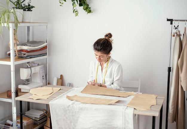Vista frontale del sarto femminile che lavora in studio