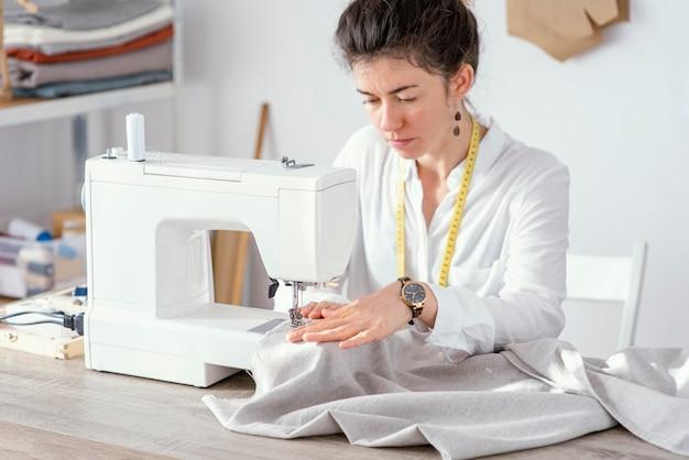 Vista frontale del sarto femminile che lavora con la macchina da cucire