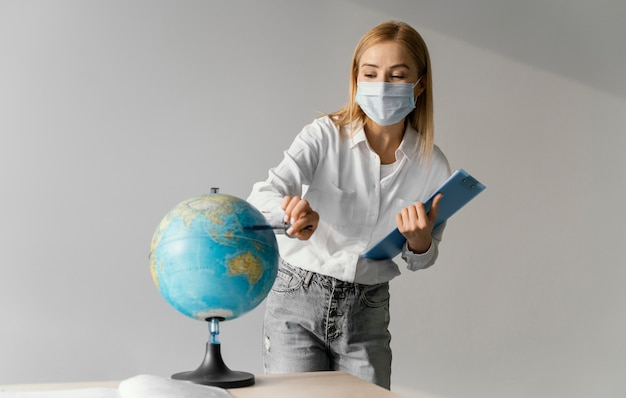 Front view of female teacher in classroom with clipboard pointing to globe