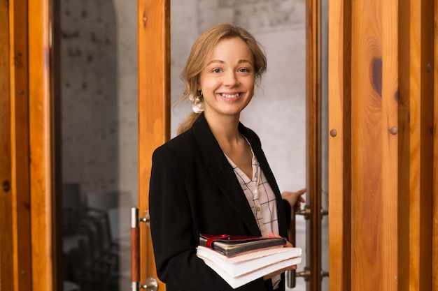 Вид спереди учительница с стопкой книг
