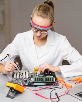 Front view of female technician with soldering iron and electronics board