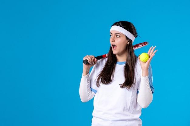 Giocatore di tennis femminile di vista frontale che tiene la racchetta e la palla di tennis