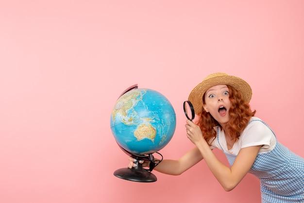 Женщина-туристка, изучающая земной шар с лупой, вид спереди