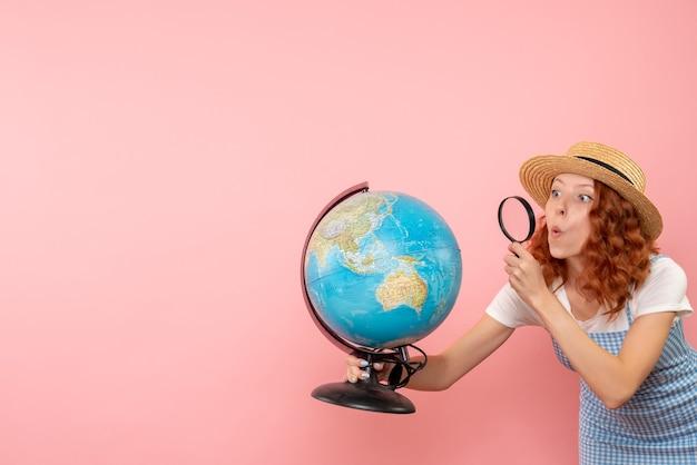 拡大鏡で地球を探索する正面図の女性観光客