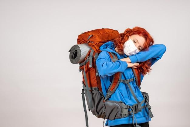 バックパックが疲れたマスクで山の旅に行く正面図の女性観光客