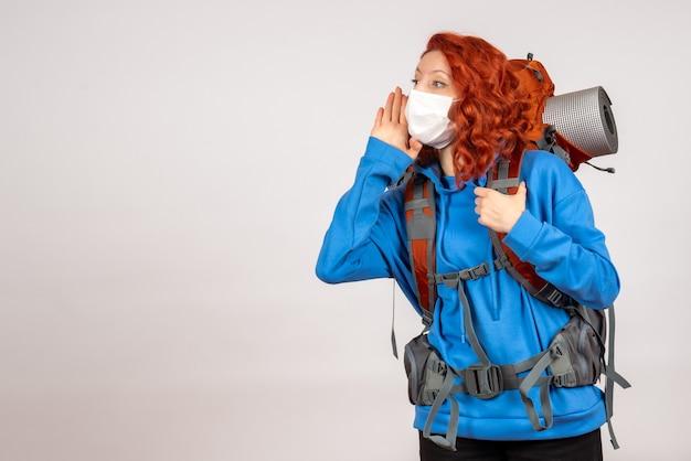 Вид спереди туристка, идущая в горное путешествие в маске с рюкзаком