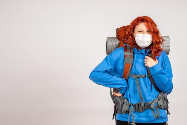Вид спереди туристка, идущая в горное путешествие в маске с рюкзаком Бесплатные Фотографии