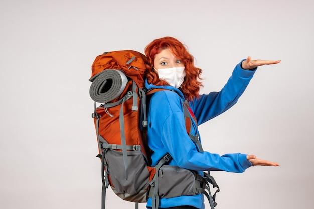 バックパックとマスクで山の旅に行く女性観光客の正面図
