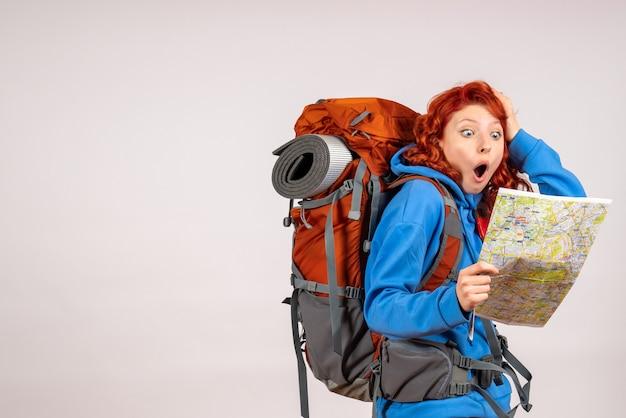 バックパックと地図で山の旅に行く正面図の女性観光客