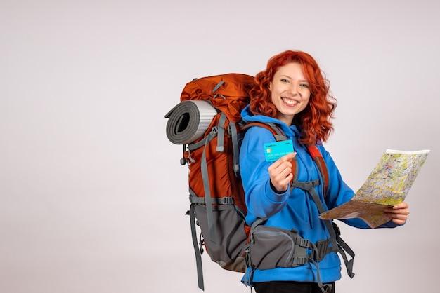 Вид спереди туристка, отправляющаяся в горное путешествие с рюкзаком и картой