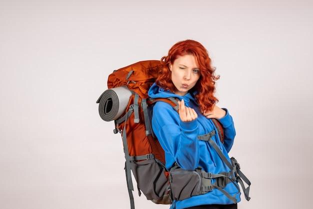 Женщина-туристка, идущая в горное путешествие с рюкзаком, вид спереди