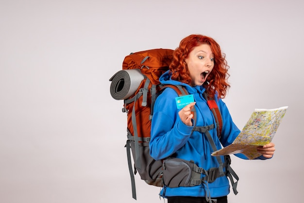 地図と銀行カードで山の旅に行く正面図の女性観光客