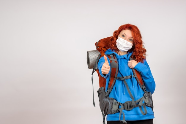 Front view female tourist going in mountain trip in mask with backpack