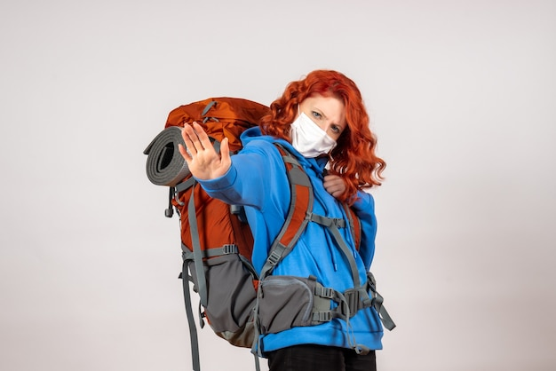 Turista femminile di vista frontale che va in viaggio in montagna in maschera con lo zaino