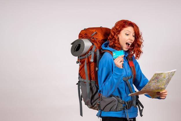 Turista femminile di vista frontale che va in viaggio in montagna con zaino e mappa