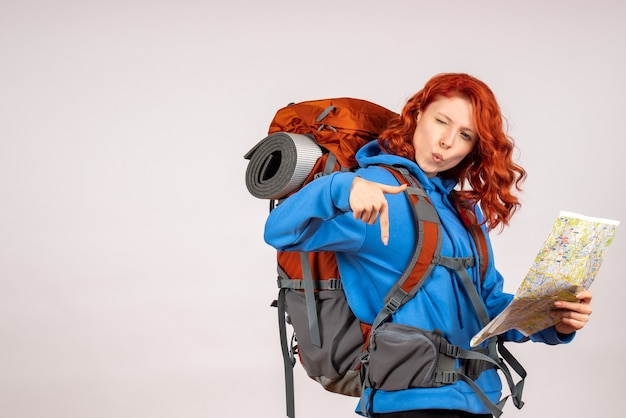 Front view female tourist going in mountain trip with backpack and map