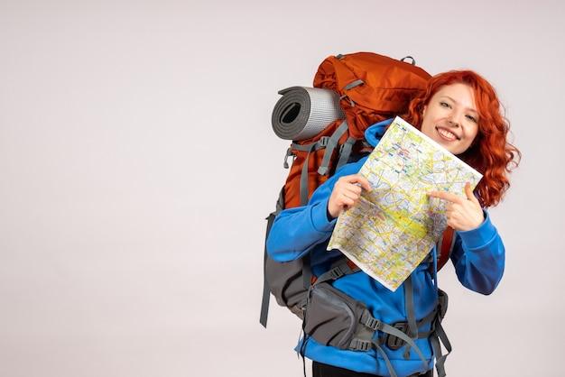 前面看在山旅行的女性游人与背包和地图