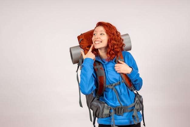 Turista femminile di vista frontale che va in viaggio di montagna con sorridere dello zaino