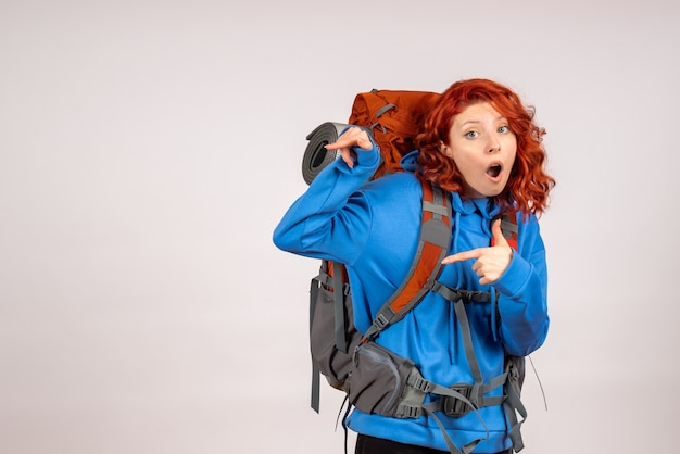 Front view female tourist going in mountain trip with backpack