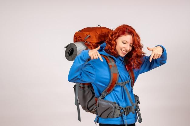 Turista femminile di vista frontale che va in viaggio di montagna con lo zaino