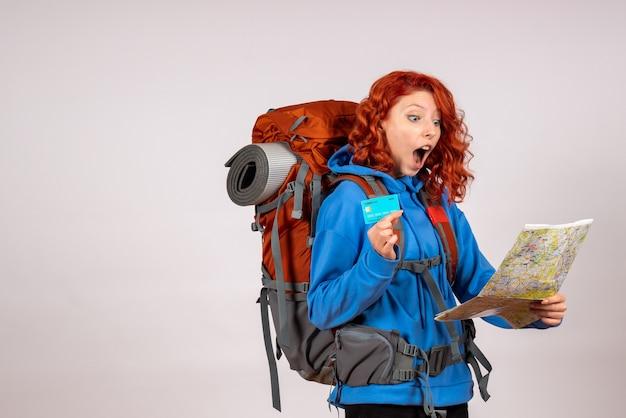 Turista femminile di vista frontale che va in viaggio in montagna con mappa e carta di credito