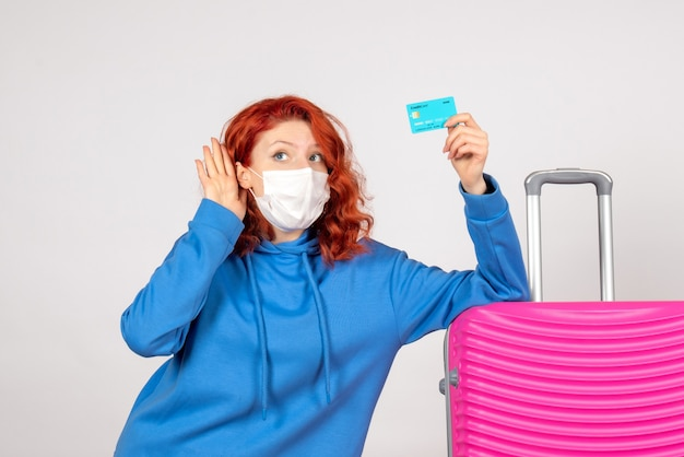 Front view female tourist holding bank card in mask