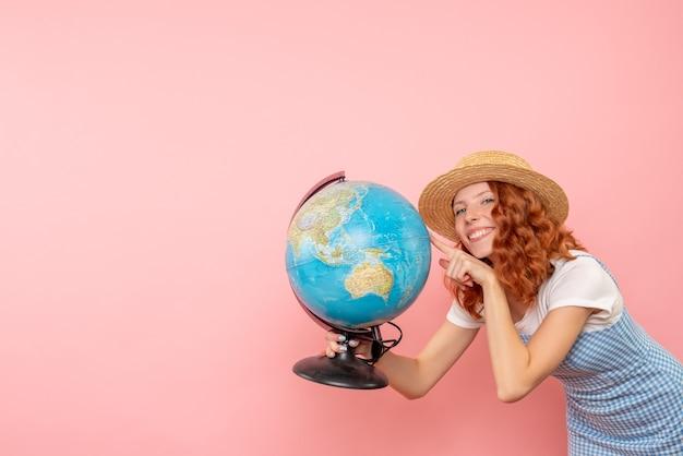Женщина-туристка, держащая земной шар, вид спереди