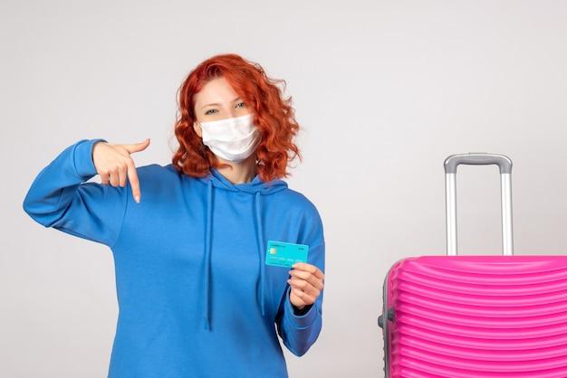 Вид спереди туристка в маске, держащая банковскую карту