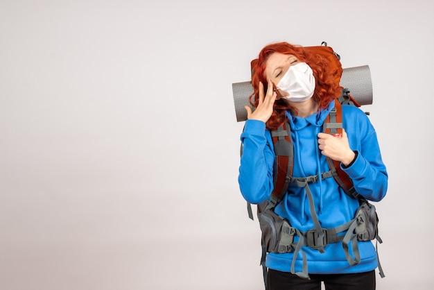 頭痛を持っているバックパックとマスクで正面図の女性観光客