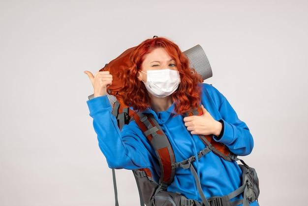 Женщина-туристка в маске с рюкзаком, вид спереди
