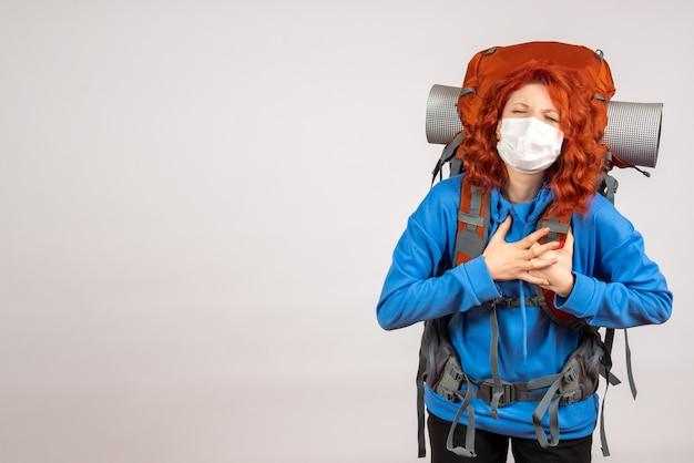バックパックとマスクで正面図の女性観光客
